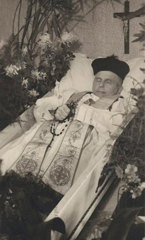 Priest in an open coffin