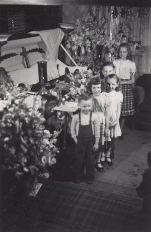 Smiling children beside an open coffin