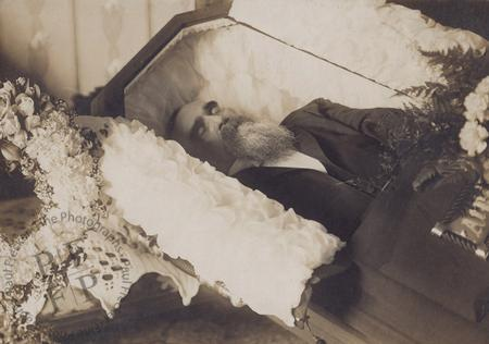 Bearded man in an open half-couch casket