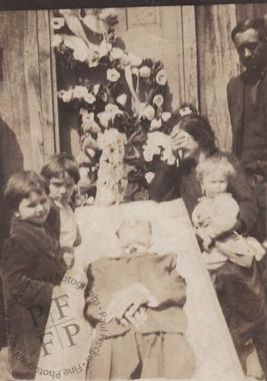 Weeping woman beside an open coffin